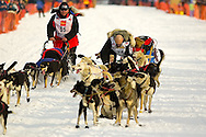 05 March 2006: Willow, Alaska - Paul Ellering, former professional wrestler, wrestles with a troublesome lead dog during the restart of the 2006 Iditarod on Willow Lake in Willow, Alaska as Ron Cortte (55) of Tomahawk, Wisc. passes him within sight of the start line.