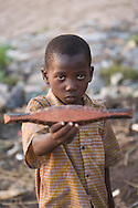 "A boy shows a miniature ""pinasse"", the tipical canoe from the regions. At the confluence of the Niger and the Bani rivers, between Timbuktu and Ségou, Mopti is the second largest city in Mali, and the hub for commerce and tourism in this west-african landlocked country."