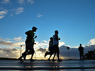 PORT ELIZABETH, SOUTH AFRICA - JULY 30: athlete on a wet road as the sun rises during the SA Half Marathon Championships on July 30, 2016 in Port Elizabeth, South Africa. (Photo by Roger Sedres/Gallo Images)