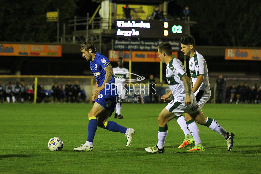 AFC Wimbledon midfielder Tom Beere (16) skips past Plymouth Argyle striker Craig Tanner (27) and Plymouth Argyle defender Connor Smith (6) during the EFL Trophy match between AFC Wimbledon and Plymouth Argyle at the Cherry Red Records Stadium, Kingston, England on 4 October 2016. Photo by Stuart Butcher.
