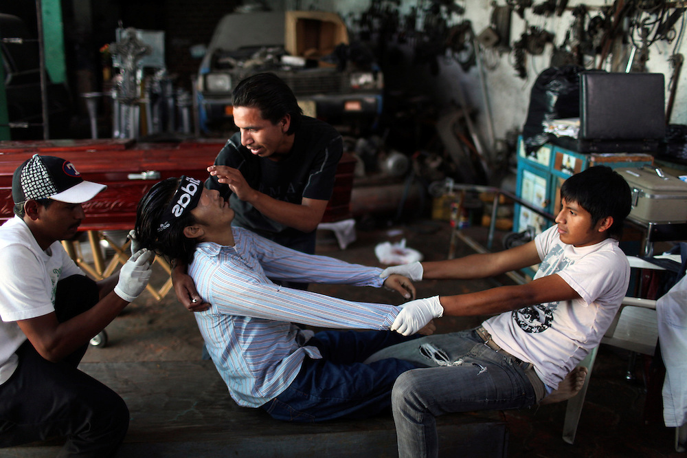 """Victor Ludwin, left, and Victor Daniel, right, tend to the body of their murdered brother Victor Barillas, 16, while their friend and funeral home employee helps them through the process in """"Valles del Sol"""" funeral home in Guatemala City, Tuesday, Nov 17,  2009. Guatemala's constant streak of murders ,17-a-day,  provide a steady flow of customers to unregulated  funeral homes, where funeral workers can embalm corpses in the back of auto repair shop or rush to crime scenes to gather information that will allow them to locate, notify and make a sales pitch to the bereaved relatives."""