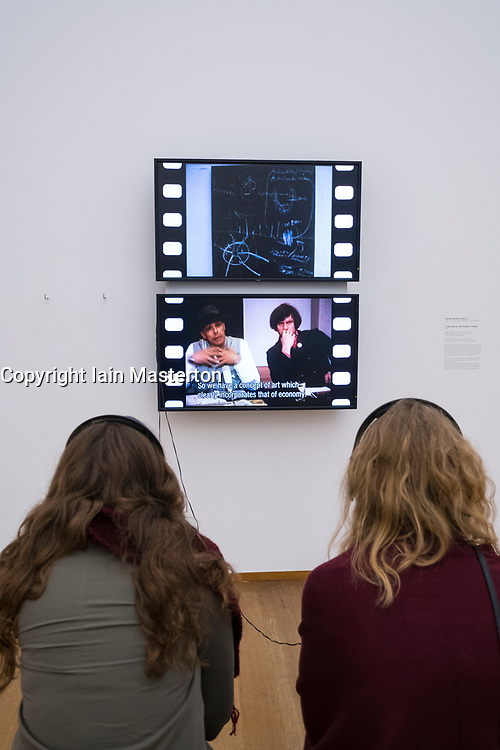 Visitors watching video installation Das Kapital/ Capital by Joseph Beuys , Babeth Mondini-VanLoo at Hamburger Bahnhof modern art museum in Berlin, Germany