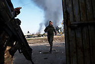 Iraq, Mosul: In Dawwasah neighbourhood an Iraqi soldier runs to avoid ISIS snipers shots as smoke rises from houses burned by ISIS fighters as they retreat. Alessio Romenzi