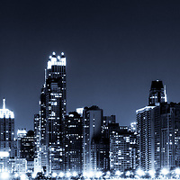 Panoramic Chicago skyline at night with blue tone. Photo panoramic ratio is 1:3. Includes Chicago downtown city buildings and the famous John Hancock Center building. The John Hancock Center is one of the world's tallest skyscrapers and is a popular fixture in the Chicago skyline.
