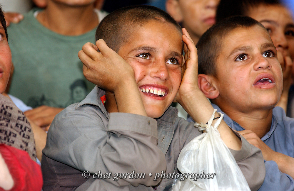 """Afghan orphaned boys watching American clown Danny Kollaja of Corpus Christi, TX as 'Lanky the Clown' during his performance at the Tahieya Maskan Orphanage for boys on Saturday, May 25, 2002. Kollaja was part of a humanitarian mission organized by The Geshundheit Instititute, founded by Dr. Hunter """"Patch"""" Adams, Lufthansa Cargo, and DHL Worldwide Express collaborated to ship medicines, food and orthopedic supplies to the Indira Ghandi Children's Hospital, clinics and orphanages in Kabul. The German NGO (Non Governmental Organization) Hammer Forum supervised the distribution of the donated supplies from various non-profit organizations in the U.S. and The Netherlands."""
