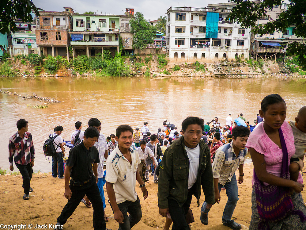 23 MAY 2013 - MAE SOT, TAK, THAILAND:  Burmese scramble up the Moei Riverbank after crossing into Thailand at an unofficial border crossing point. Myawaddy is in the background. Fifty years of political turmoil in Burma (Myanmar) has led millions of Burmese to leave their country. Many have settled in neighboring Thailand. Mae Sot, on the Mae Nam Moei (Moei River) is the center of the Burmese emigre community in central western Thailand. There are hundreds of thousands of Burmese refugees and migrants in the area. Many live a shadowy existence without papers and without recourse if they cross Thai authorities. The Burmese have their own schools and hospitals (with funding provided by NGOs). Burmese restaurants and tea houses are common in the area.    PHOTO BY JACK KURTZ