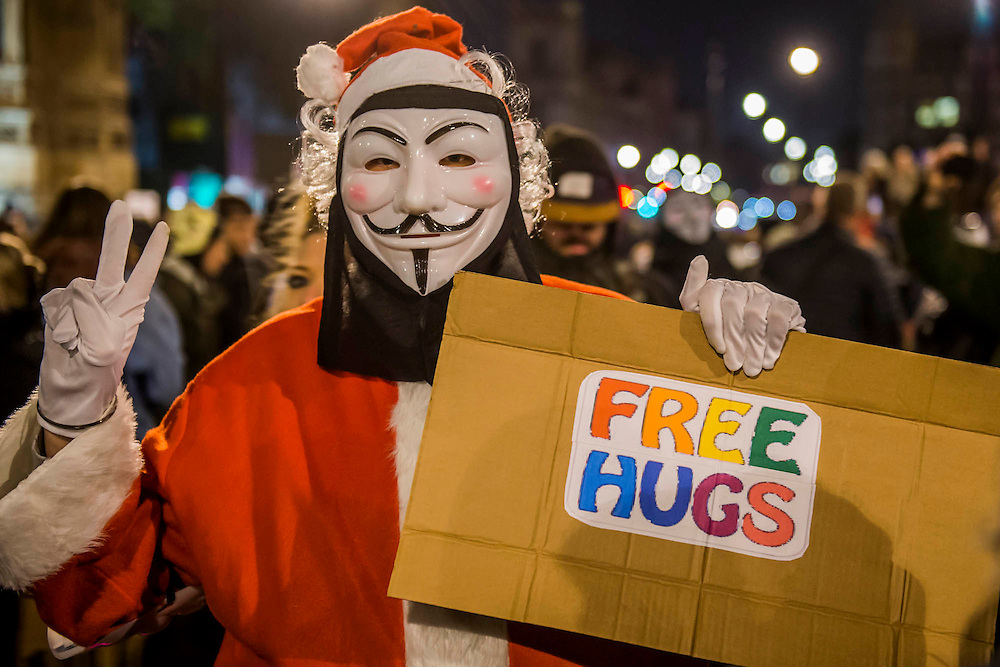 "Santa gives out free hugs - The Million Mask March - anti-establishment protesters in V for Vendetta-inspired Guy Fawkes masks march from Trafalgar Square to Parliament Square. It was organised by Anonymous, the anarchic 'hacktivist' network. The movement is also closely identified with the Occupy protests, Wikileaks, and the Arab Spring. The UK Anonymous website describes the march on Parliament as a ""protest against austerity … the infringement of our rights … mass surveillance … war crimes … corrupt politicians."""
