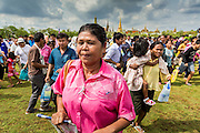 13 MAY 2013 - BANGKOK, THAILAND: People rush onto the field at the Royal Ploughing Ceremony in Bangkok. After the ceremony, thousands of Thais, mostly family formers, rush onto the ploughed ground to gather up the blessed rice seeds sown by the Brahmin priests. The Royal Plowing Ceremony is held Thailand to mark the traditional beginning of the rice-growing season. The date is usually in May, but is determined by court astrologers and varies year to year. During the ceremony, two sacred oxen are hitched to a wooden plough and plough a small field on Sanam Luang (across from the Grand Palace), while rice seed is sown by court Brahmins. After the ploughing, the oxen are offered plates of food, including rice, corn, green beans, sesame, fresh-cut grass, water and rice whisky. Depending on what the oxen eat, court astrologers and Brahmins make a prediction on whether the coming growing season will be bountiful or not. The ceremony is rooted in Brahman belief, and is held to ensure a good harvest. A similar ceremony is held in Cambodia.    PHOTO BY JACK KURTZ