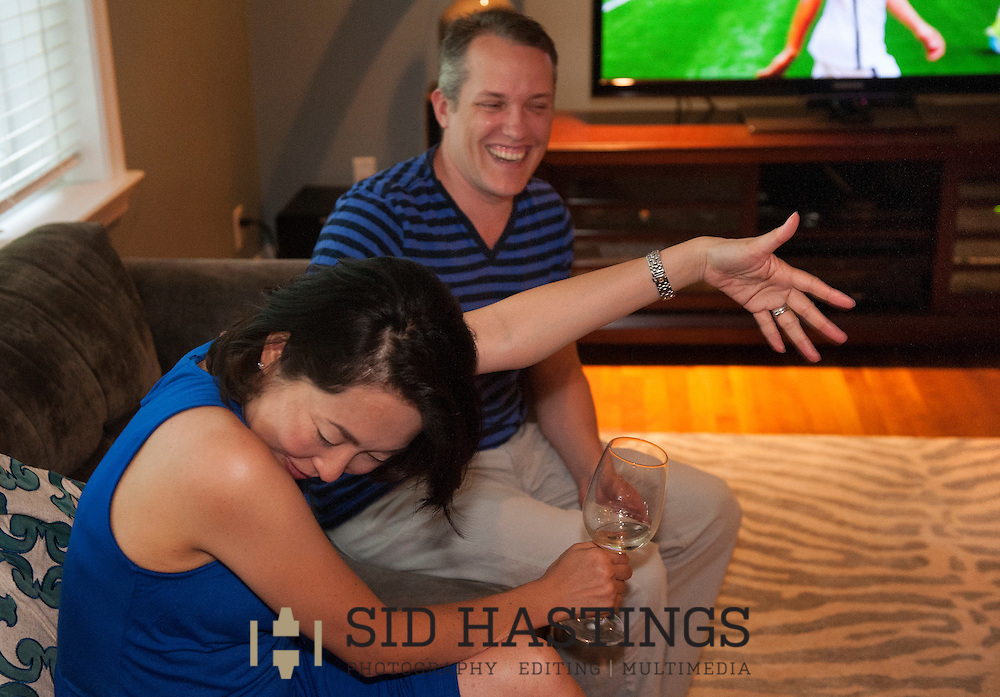 5 JULY 2015 -- OLIVETTE, Mo. -- Mayumi Bollman (front), a native of Japan, reacts to good-natured joking by her husband Gary Bollman at halftime of the 2015 Women's World Cup Final between the US and Japan during a party at their Olivette, Mo. home Sunday, July 5, 2015. The party brought together international couples from the St. Louis area, couples with one spouse native to Japan and one native to the US. The US led Japan 4-1 at halftime and won the game 5-2 to claim the World Cup. Photo © copyright 2015 Sid Hastings.