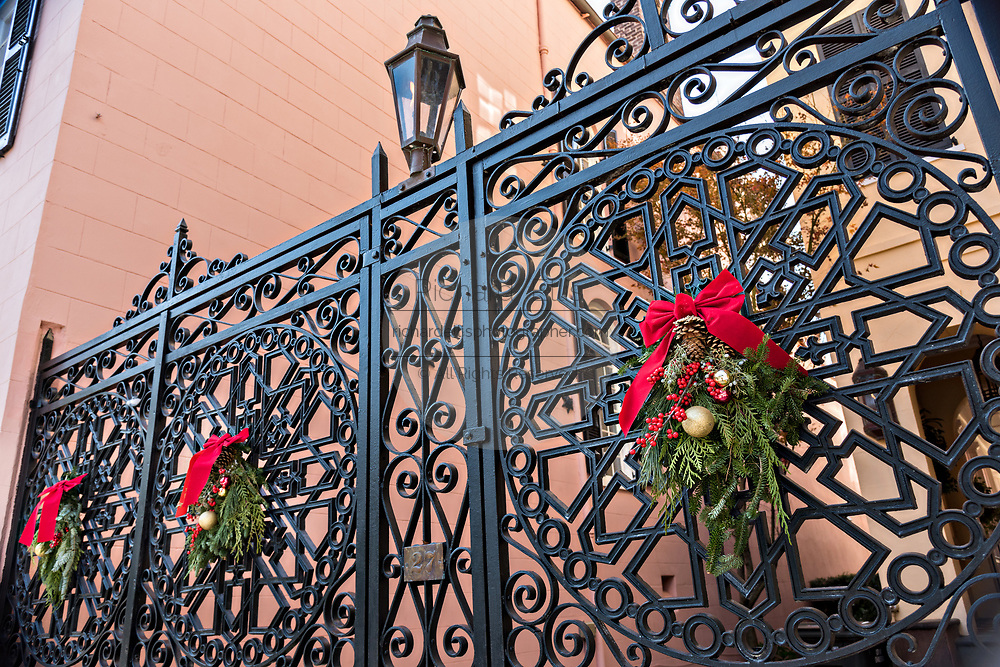 A wrought iron gate of a historic home decorated with Christmas wreaths on Meeting Street in Charleston, SC.