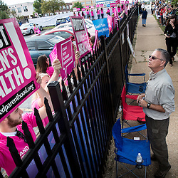 Lisa Johnston | lisajohnston@archstl.org  | Twitter: @aeternusphoto John Ryan with Defenders of the Unborn talked through the  fence to Planned Parenthood supporters in an effort to dialog with them about life issues.   About 450 pro-life supporters stood outside of Planned Parenthood in prayer after a Mass celebrated at the Cathedral Basilica.  A Rosary procession to Planned Parenthood on Forest Park Avenue followed.  Pro-lifer's were met by pink signs held by counter protesters supporting the abortion provider. Supporters of the abortion provided held signs behind a recently modified fence meant to obscure their view.