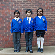 """Southall, Greater London, UK, January 27, 2015. <br /> Change comes from education. At the """"Dominion Centre & Library"""", in Southall, three schoolgirls from Punjabi and Srilankan origin are proud to be photographed in their school uniform. The 9-year old brother of one of the girls is shocked: why should girls be photographed?"""