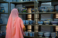 A woman in a sari in the Kripal Kumbh shop selling blue pottery in Jaipur, Rajasthan, India