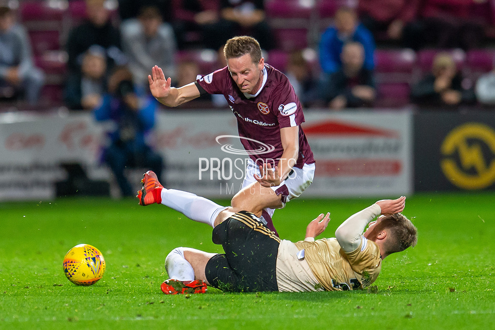 Dean Campbell (#24) of Aberdeen FC slide tackles Steven MacLean (#18) of Heart of Midlothian FC during the Betfred Scottish Football League Cup quarter final match between Heart of Midlothian FC and Aberdeen FC at Tynecastle Stadium, Edinburgh, Scotland on 25 September 2019.