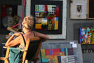 Artist sits in booth amid her paintings at the St. Louis Art Fair, renowned for high-end works in all media; Clayton, Missouri.