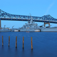 New England war memorial photography of Battleship Cove below the Braga Bridge in Fall River Massachusetts. This maritime landmark features the world&rsquo;s largest collection of World War II naval vessels. The dominant battleship is the USS Massachusetts BB-59.<br />
