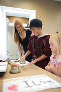 Visiting Art Instructor Elizabeth Ferrill observes  Tyler Thompson, 10 (Center) as he makes a print at Fall Family Day at the Kennedy Museum of Art on Saturday, September 29.