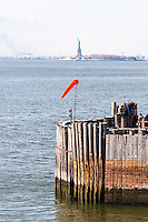 US, New York City. South Ferry pier, Statue of Liberty in the background. Repair work.