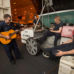 USS John C Stennis CVN-74 Aircraft Carrier.Pic Shows Hangar Personnel relax with a guitar