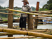 16 SEPTEMBER 2014 - SANGKHLA BURI, KANCHANABURI, THAILAND: A Mon community leader watches the repair of the Mon Bridge from a floating bamboo raft beneath the bridge. The 2800 foot long (850 meters) Saphan Mon (Mon Bridge) spans the Song Kalia River. It is reportedly second longest wooden bridge in the world. The bridge was severely damaged during heavy rainfall in July 2013 when its 230 foot middle section  (70 meters) collapsed during flooding. Officially known as Uttamanusorn Bridge, the bridge has been used by people in Sangkhla Buri (also known as Sangkhlaburi) for 20 years. The bridge was was conceived by Luang Pho Uttama, the late abbot of of Wat Wang Wiwekaram, and was built by hand by Mon refugees from Myanmar (then Burma). The wooden bridge is one of the leading tourist attractions in Kanchanaburi province. The loss of the bridge has hurt the economy of the Mon community opposite Sangkhla Buri. The repair has taken far longer than expected. Thai Prime Minister General Prayuth Chan-ocha ordered an engineer unit of the Royal Thai Army to help the local Mon population repair the bridge. Local people said they hope the bridge is repaired by the end November, which is when the tourist season starts.    PHOTO BY JACK KURTZ
