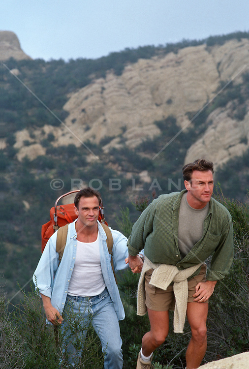 Two men holding hands hiking in the Santa Monica mountains