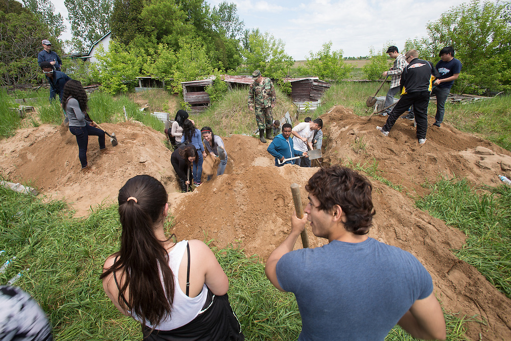 Tillsonburg, Ontario ---2014-05-30--- Students from Central Commerce Collegiate high school in Toronto dig a trench as Robin Barker-James shouts instructions during a field trip to the  Bill Findley Outdoor Education Centre in Tillsonburg, Ontario, May 30, 2014 where the students learned what it was like to be a soldier in the trenches in World War 1.<br /> GEOFF ROBINS Toronto Star