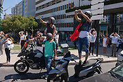 Motorists and bike riders join pedestrian crowds to watch the Portugal football team during their victory procession the day after the Euro 2016 final with France.