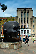 Fernando Botero's sculpture, 'The Head', dominates the scene in Plaza Botero.  The art deco Museum of Antioquia stands in the background.