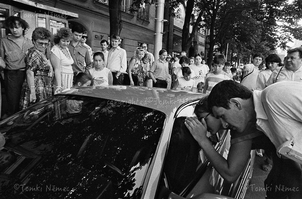 CESKOSLOVENSKO 80s - Ceskoslovenska socialisticka republika<br /> &quot;Lid&quot; si prohlizi  automobil zapadni vyroby, zaparkovany pred hotelem Jalta? na Vaclavskem namesti v Praze