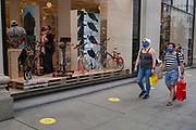 On the day that covid pandemic guidelines for shoppers in England mean that the wearing of face coverings in shops is mandatory, shoppers wearing face masks carry Selfridges shopping bags, on 24th July 2020, in London, England.