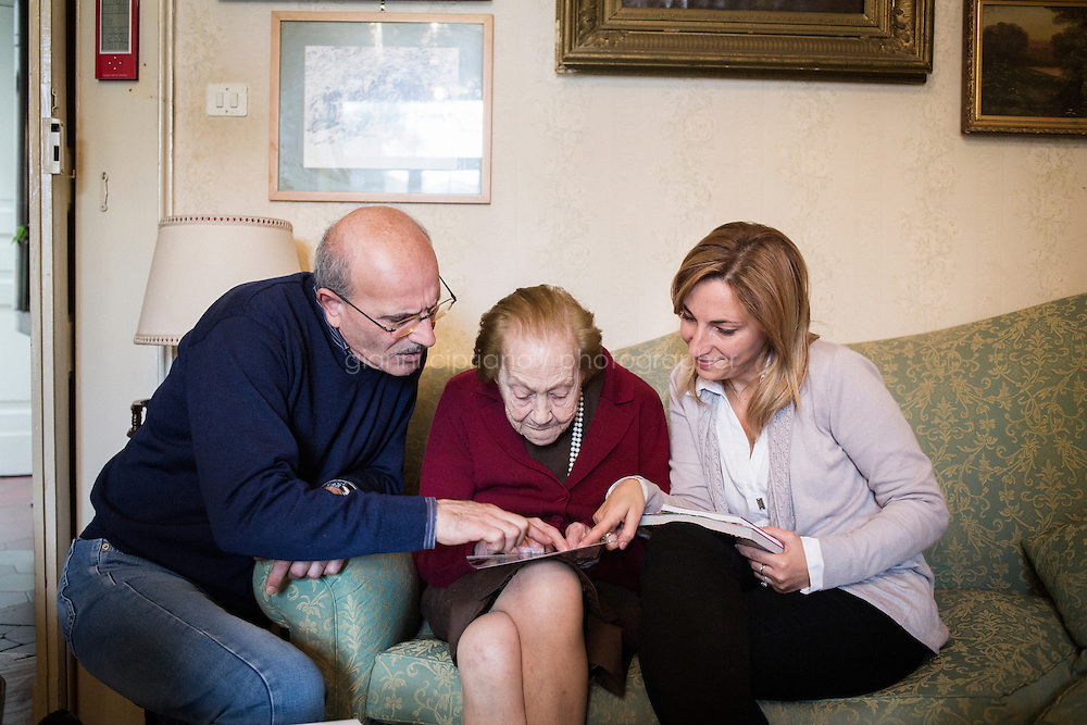 SANT'AGATA DE' GOTI, ITALY - 13 November 2013: Adele Mongillo (center), the sister-in-law Mayor of New York Bill De Blasio's uncle and closest relative in Italy, together with Fausto Iannotta (left, 56) who did a research on the De Blasio's, and Roberta Mongillo (right, 37), sit on a couch looking at family pictures of the De Blasio's at her home in Sant'Agata de' Goti, Italy, on November 13th, 2013. &ldquo;Billy was always a bright, attentive and affectionate boy,&rdquo; Adele Mongillo said, sitting on her antique couch. &ldquo;He is the right man at the right time.&rdquo;<br /> &ldquo;His love for this land comes from his grandfather,&rdquo; she added. &ldquo;He loved it here.&rdquo;<br /> <br /> Sant'Agata de' Goti is the town that Bill de Blasio&rsquo;s maternal grandfather, Giovanni de Blasio, left over a<br /> hundred years ago for the United States. sits on her couch at her home in Sant'Agata de' Goti, Italy, on November 13th, 2013. &ldquo;Billy was always a bright, attentive and affectionate boy,&rdquo; Adele Mongillo said, sitting on her antique couch. &ldquo;He is the right man at the right time.&rdquo;<br /> &ldquo;His love for this land comes from his grandfather,&rdquo; she added. &ldquo;He loved it here.&rdquo;<br /> <br /> Sant'Agata de' Goti is the town that Bill de Blasio&rsquo;s maternal grandfather, Giovanni de Blasio, left over a<br /> hundred years ago for the United States.