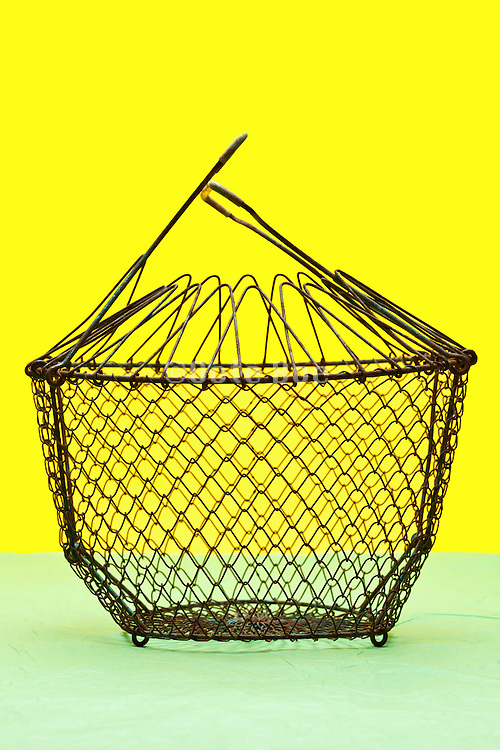 vintage wire salad basket object on yellow green background
