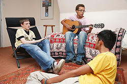 Group of youths in a bedroom with a guitar.
