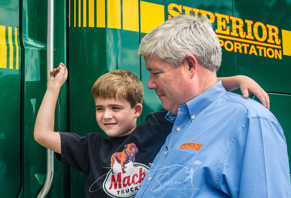 Pat Barber helps his son, James Barber, climb onto a Mack truck at Superior Transportation, Sept. 30, 2015, in North Charleston, South Carolina. Pat Barber started the company in 1998. James, 6, is already showing a big interest in the company and its Mack trucks, and Barber says he hopes he will follow in his footsteps and carry on the family legacy.  (Photo by Carmen K. Sisson/Cloudybright)