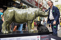 "**CAPTION CORRECTION - Rhino statues are 750mm tall, not 750cm tall, as stated in previous captions**<br /> © Licensed to London News Pictures. 20/08/2018. LONDON, UK. Adam Dant stands in Carnaby Street with his painted rhino ""A.D's Rhino"" during a photocall.  At 750mm tall and weighing 300 kg, each rhino has been specially embellished by an internationally renowned artist.  21 rhinos are in place at a popular location in central London, forming the Tusk Rhino Trail, until World Rhino Day on 22 September to raise awareness of the severe threat of poaching to the species' survival.  They will then be auctioned by Christie's on 9 October to raise funds for the Tusk animal conservation charity.  Photo credit: Stephen Chung/LNP"
