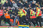 A supporter in a 'Scream' mask is escorted off the pitch during the EFL Cup 4th round match between West Ham United and Tottenham Hotspur at the London Stadium, London, England on 31 October 2018.