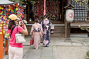 two traditionally dressed woman going to a shrine with tourist filming