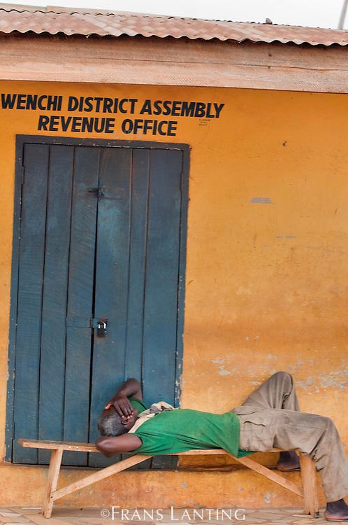 Man sleeping outside tax revenue office, Ghana