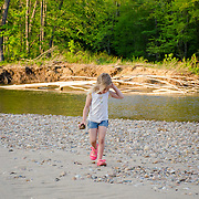 A young girl looks for interesting stones along the banks of the Saco River, North Conway, NH