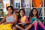 Left to right: Janaira, Giovana and Ketlin smiling at the camera as they sit on the floor looking at books in the community library, Biblioteca Comunitaria do Arquipelago, Porte Alegre, Brazil. <br /> <br /> Cirandar is working in partnership with  C&A and C&A Instituto to implement a network of Community Libraries in eight communities of Porto Alegre.