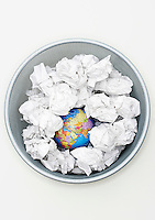 Waste bin with globe among crumpled papers view from above