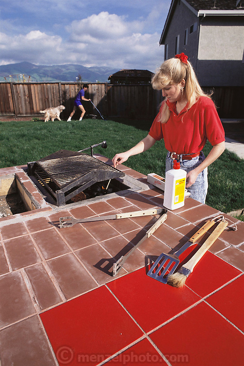 Couple getting ready for a barbeque in their new suburban home, Fremont, California (starting fire, mowing lawn). MODEL RELEASED.