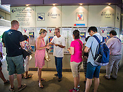 28 OCTOBER 2014 - BANGKOK, THAILAND:  Passengers line up at the ticket machines in the BTS Saphan Taksin station. The Skytrain (called the BTS) system has a combined length of 36 kilometres and includes 34 stations, including Saphan Taksin. While there are two train tracks for most stretches of the Skytrain system, the portion on the Saphan Taksin Bridge spanning the Chao Phraya River has just one track due to limited space, causing a bottleneck when an outbound train and inbound train arrive at the bridge at the same time. The Bangkok Metropolitan Authority (BMA) had sought permission from the Department of Rural Roads to expand the Taksin Bridge in order to make way for an additional track, but the department had said it was not possible. The Saphan Taksin  station was originally supposed to be temporary and is one of the busiest on the system. It's a connecting station for the Chao Phraya River boats used by Thai commuters coming into the city from neighboring provinces and tourists who use the boats to go upriver into the old parts of Bangkok from the central business district. More than 4,000 commuters a day use the station. The BMA plans to build an elevated moving sidewalk to the river from Surasak BTS station about one kilometer away. Surasak is the nearest station to Saphan Taksin. The Skytrain system has a combined length of 36 kilometres and includes 34 stations, including Saphan Taksin.       PHOTO BY JACK KURTZ