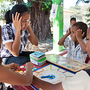 Joanina Quintao reads a picture book with animals with a small boy. Joanina is a newly graduated teacher who believes in interaction with children and learning through play. The Alola Foundation provide pre-school play and learn sessions. Education in Timor-Leste is very basic with classes up to 80 children and teachers trained under an old fashined system with very little inter-action between teacher and pupils..Fundasaun Alola is a not for profit non government organization operating in Timor Leste to improve the lives of women and children. Founded in 2001 by the then First Lady, Ms Kirsty Sword Gusmao, the organization seeks to nurture women leaders and advocate for the rights of women.