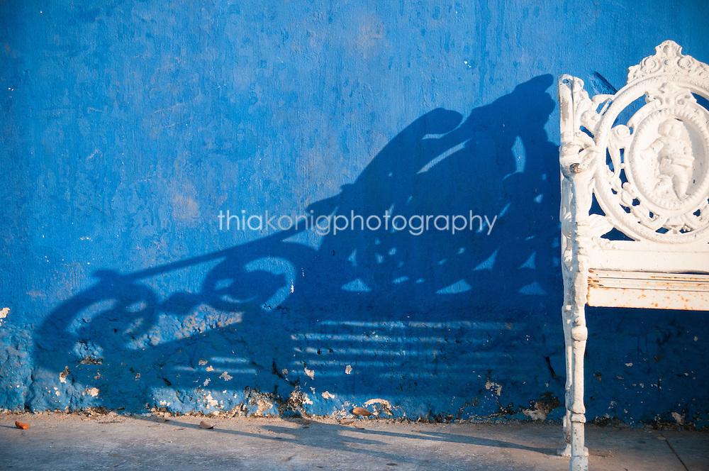 Ornate white bench casts a long shadow on a blue wall, Barra de Navidad, Mexico