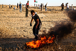 "November 2, 2018 - Palestinian protesters clash with the Israeli army near the fence in the ""Abu Safiya"" area east of Jabalia in the northern Gaza Strip during the Great March of Return rally on 2th November 2018. Thousands of demonstrators attended several sites along the Gaza border with Israel this Friday, with some advancing and hurling stones towards the fence, and according to the Gaza Health Ministry a number of protesters were injured by Israeli live fire and tear gas. The March has taken place while Egyptian mediators are working to lower tension along the Gaza-Israeli frontier after months of protests and deadly clashes. Since March 2018 thousands of Gaza demonstrators have gathered every Friday along the border in protest against the Israeli siege on Gaza and in support of the right of Palestinian refugees to return the land lost around the founding of Israel in 1948. At least 214 Palestinians have been killed by Israeli fire since the protests started while several thousands have been injured by Israeli live ammunition and tear gas. One Israeli soldier has also been killed since the protests began (Credit Image: © Ahmad Hasaballah/IMAGESLIVE via ZUMA Wire)"