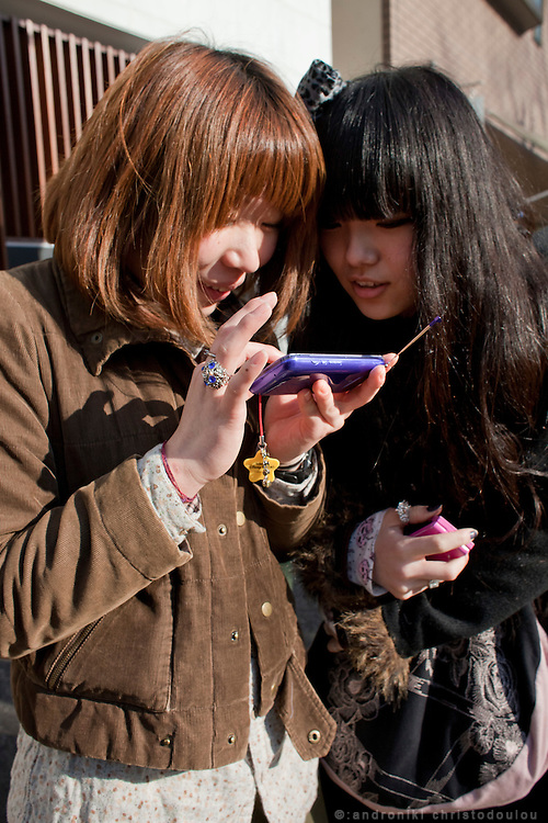 Japanese girls checking information about the strong eathquake that just happened, on internet via their mobile phone, while they are at a park in Ebisu waiting for the aftershocks to stop.