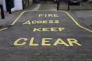 Keep Clear for fire access markings on cobbles outside residential buildings in a north London side street.