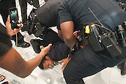 A demonstrator is thrown to the ground and arrested outside Atlanta city council chambers during a protest against the closing of the Peachtree-Pine homesless shelter.