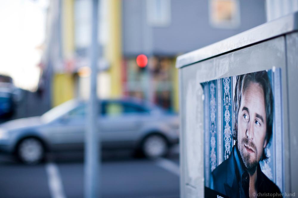 A poster of singer Geir Ólafsson in 101 Reykjavík. It looks like he is watching the car that is passing by. Geir Ólafsson fylgist með umferðinni í 101.